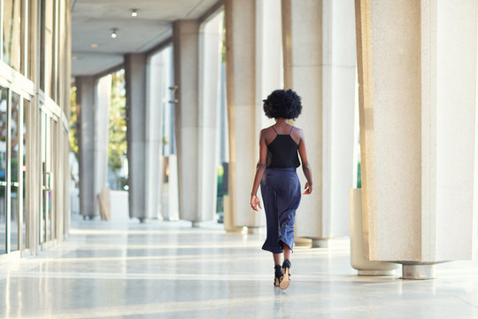 A young fashionable Afro-American woman walking away from the camera