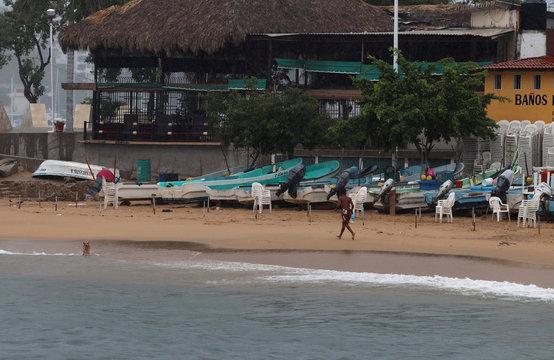 A man runs at a beach during Tropical Storm Lorena in Acapulco