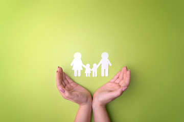 Female tender hands with a family symbol cut out of white paper. Protecting the rights of people and sexual minorities. Love for the children of the world on earth, a clean ecology. View from above.