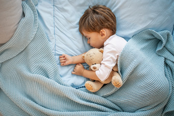 Sweet little boy sleeps with a toy. Young boy in bed sleeping and hug teddy bear. Little boy, big dreamer. It's bedtime for baby and bear. With teddy close by he has the softest sweetest dreams