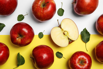 Flat lay composition with ripe juicy red apples and leaves on color background