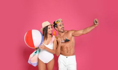 Young attractive couple in beachwear with snorkel and ball taking selfie on pink background