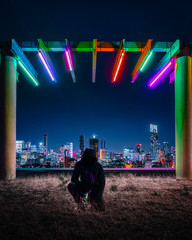 A man kneeling below a neon overhand with a city in the bacgkground.