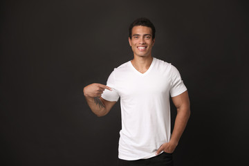 Handsome young African-American man in blank t-shirt on black background. Space for design Fototapete