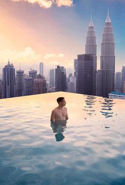Man in infinity pool on rooftop