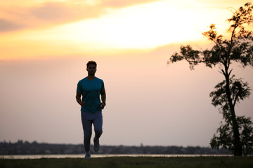 Young man running outdoors in evening. Space for text