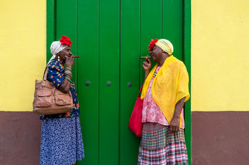Photo sur Plexiglas La Havane Two Old Cuban ladies smoking a large cigar in La Havana, Cuba