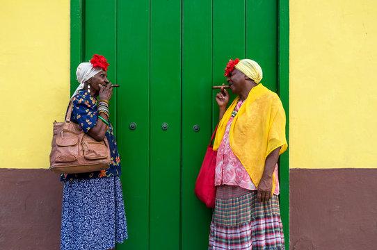 Two Old Cuban ladies smoking a large cigar in La Havana, Cuba