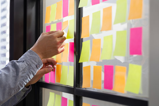 IT worker tracking his tasks on kanban board. Using task control of agile development methodology. Man attaching sticky note to scrum task board in the office