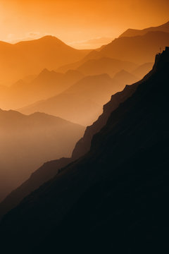 Mountain peaks through an orange haze.