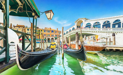 Panoramic view of Gondolas and boat at their moorings against famous Rialto Bridge at Grand Canal in Venice, Italy, Europe