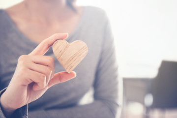 Female hand holding a wood heart shape, copy space.