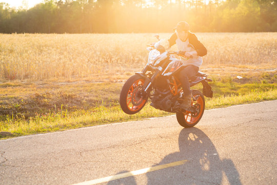 Teenage boy on a dirtbike motorcycle doing a wheelie at sunset