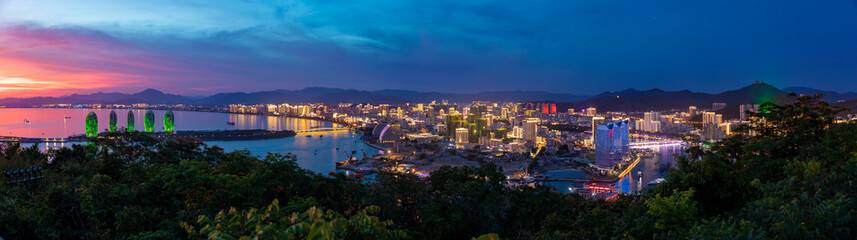 Night view of Phoenix island and Sanya city illuminated with city lights. View from Luhuitou Park on Hainan Island, China