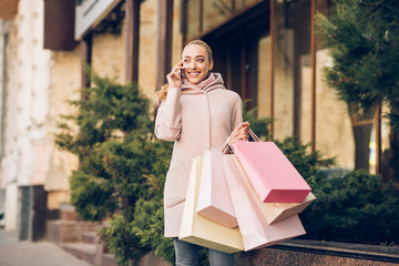 Happy fashion woman talking on cellphone after shopping
