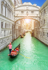 Bridge of Sighs (Ponte dei Sospiri) and row of gondolas with gondoliers and Rio de Palazzo o de Canonica Canal from Riva degli Schiavoni in Venice, Italy, in sunrise morning light