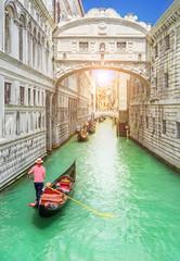 Bridge of Sighs (Ponte dei Sospiri) and row of gondolas with gondoliers and Rio de Palazzo o de Canonica Canal from Riva degli Schiavoni in Venice, Italy, in sunrise morning light