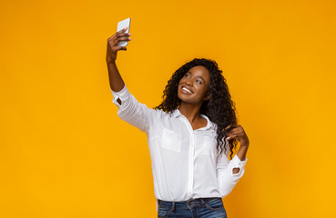 Cheerful african girl holding cellphone and making selfie