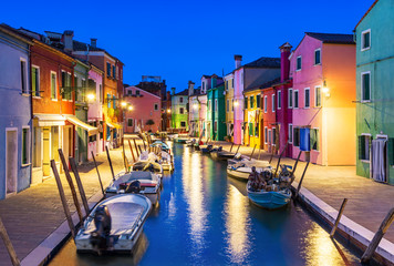 Burano island at night, Venice, Venetian Lagoon, Italy. Colourfully painted houses facades along the small beautiful canal with boats.