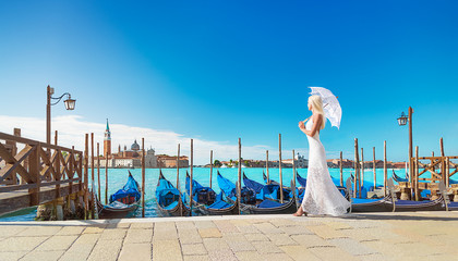 Cute blonde woman in white dress with umbrella walking in Venice against panoramic view of Gondolas at their moorings, famous San Giorgio Maggiore island and church. Italy, Europe