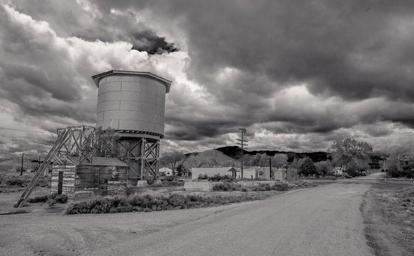 Grayscale photography of house and water tank