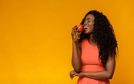 Happy african american woman enjoying red apple