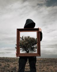 Man holding brown wooden frame