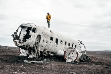 Man standing on plane wreck against sky