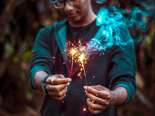 Person holding sparklers in both hands
