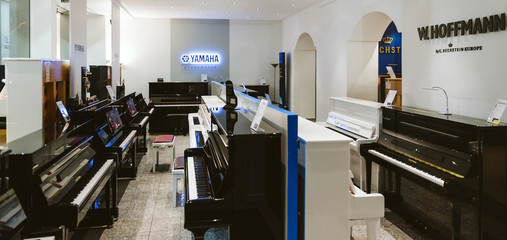 TRIER, GERMANY - FEB 21, 2015: Wide image with luxury piano shop musical instrument store selling exclusive pianos and royal grand piano by W.Hoffmann by C. Bechsteinand Yamaha Pianoworld