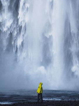 Person wearing yellow raincoat near waterfall