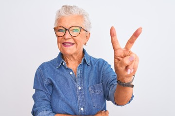 Senior grey-haired woman wearing denim shirt and glasses over isolated white background smiling with happy face winking at the camera doing victory sign with fingers. Number two.