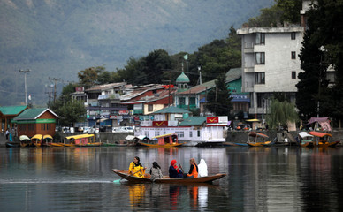 Women row a small boat in the waters of Dal lake in Srinagar