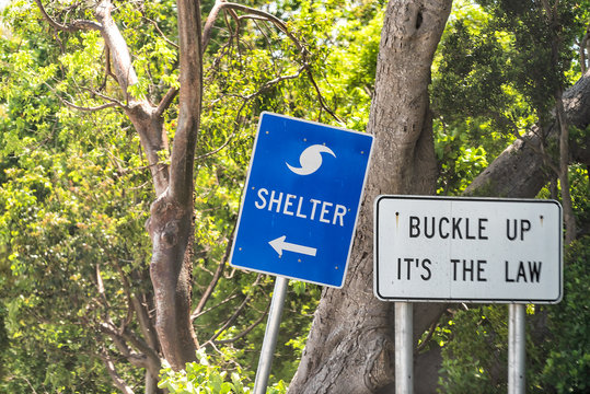 Hurricane evacuation shelter blue sign on road and seat belt buckle up it's the law text with arrow direction in Naples, Florida coast during day