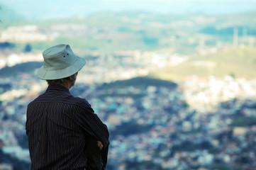 homem de chapéu olhando a cidade