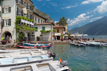 Fotobehang Alpen LIMONE SUL GARDA, ITALY - JUNE 13, 2019: The little harbor under the alps rocks on the Lago di Garda lake.
