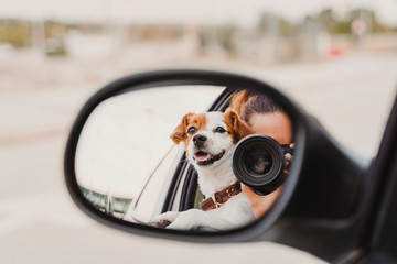 young woman taking a picture with camera on rear mirror of her cute small jack russell dog watching by the window. Ready to travel. Traveling with pets concept