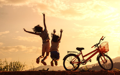 Silhouette of happy children jumping playing on mountain at sunset sky background