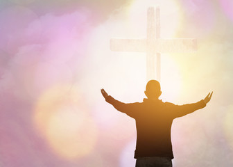 soft focus and Silhouettes of man raise hand up worship God over the cross in cloudy sky . Christian background with copy space for your text
