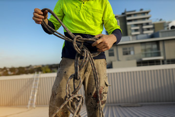 Closeup pic of rope access abseiler construction worker standing on top of the roof conducting safety inspecting uncoiling twisting rope prior used construction site Sydney, Australia