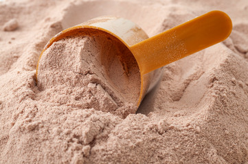 Exercising , weight loss shake and muscle gain conceptual idea with close up on scoop of chocolate flavoured post workout whey protein powder