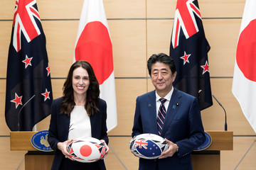 New Zealand's Prime Minister Jacinda Ardern and Japan's Prime Minister Shinzo Abe hold rugby balls after a joint press conference on Sept. 19, 2019 in Tokyo