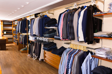 Fashion modern men clothes displayed on shelves and hanger racks in clothing store