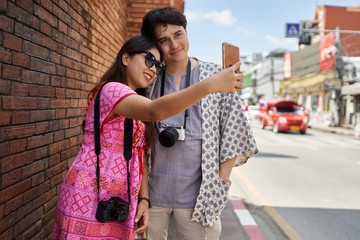 thai couple sightseeing around historical chiang mai near old city wall looking at photos on camera