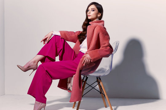 High fashion portrait of young elegant woman. Coral coat, magenta pants, white blouse.