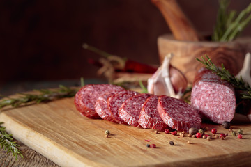 Fototapete - Smoked salami on a old wooden table.