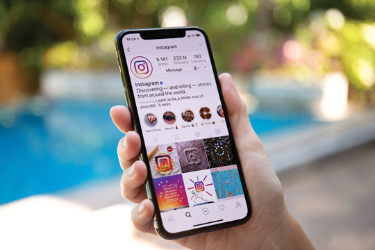 Woman hand holding iPhone X with social networking service Instagram