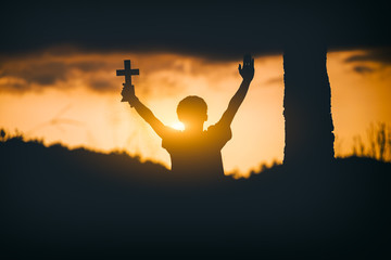 Young man sitting and lift hands for worshipping God with cross at sunset background. christian silhouette concept.