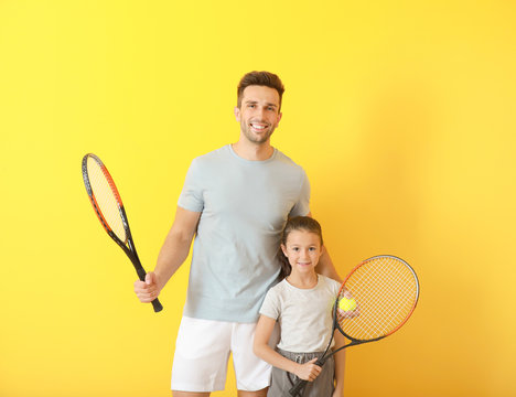 Little girl and her father with tennis rackets on color background
