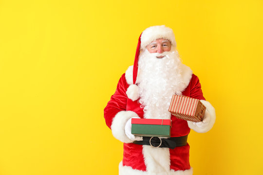 Santa Claus with gifts on color background